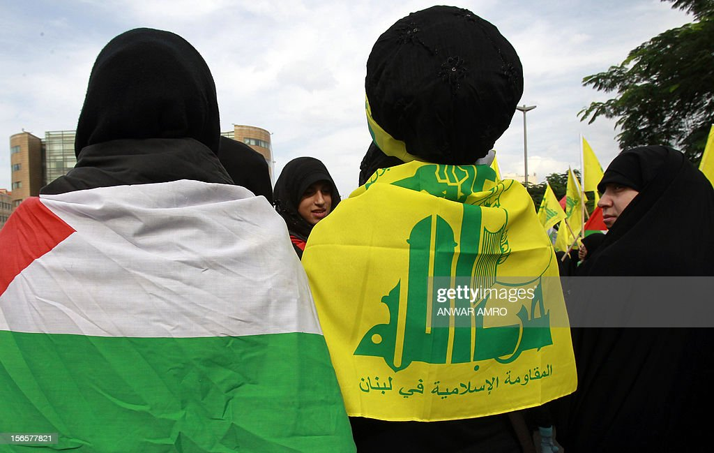 Lebanese protestors wearing the Hezbollah flag and another wearing the Palestinian flag gather during a protest against the ongoing attack on Gaza outside the offices of the United Nations Economic and Social Commission for Western Asia (ESCWA) in Lebanese capital Beirut, on November 17, 2012. Lebanese political factions alongside their Palestinian counterparts gathered in the Lebanese capital, as the ongoing assault on Gaza strip took the death toll from three days of Israeli raids to 40, medics said. AFP PHOTO / ANWAR AMRO