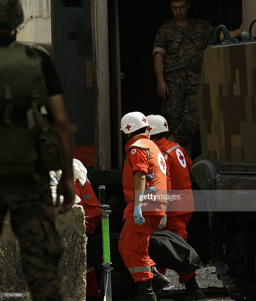 Lebanese Red Cross members carry a body from the Bilal bin Rabah mosque in the Abra district of the southern city of Sidon on June 25, 2013, after troops seized control of the headquarters of a radical Sunni sheikh whose supporters battled the army for two days, killing 16 soldiers.