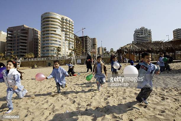Lebanese school children run with the balloons on Beirut's Ramlet alBaida beach on January 20 as the foreign ministers of Turkey and Qatar suspended...