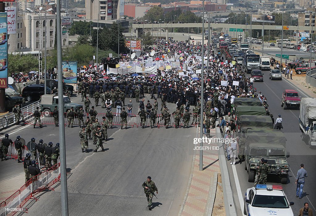 Lebanese security forces stand guard on a main highway as public sector employees protest near the presidential palace in Baabda east of Lebanon's capital Beirut on March 21, 2013 to demand an increase in wages.
