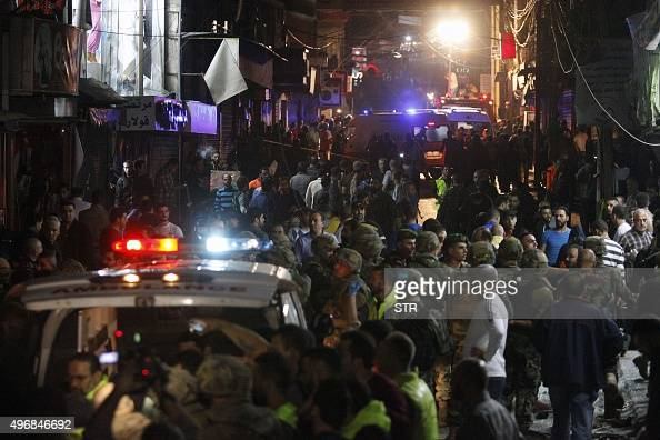 Lebanese security personnel and citizens gather at the scene of a twin suicide bombing that rocked a busy shopping street a Beirut stronghold of...