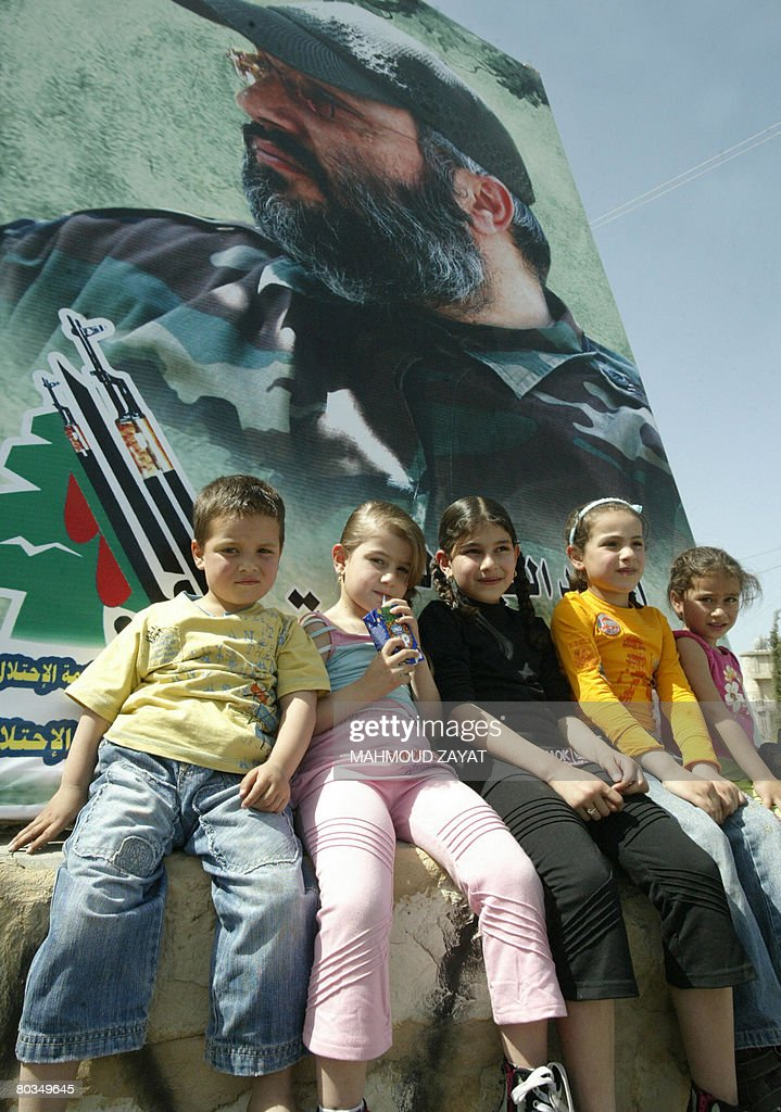 Lebanese Shiite children sit under a huge portrait of Imad Mughnieh during a memorial ceremony held for the Hezbollah's slain commander in the...