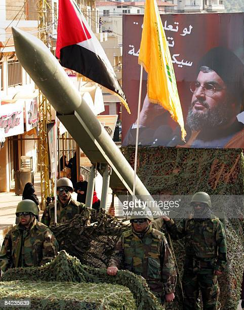 Lebanese Shiite Hezbollah militants guard a missile as a picture of the movement's chief Hassan Nasrallah is seen during an annual parade in the...