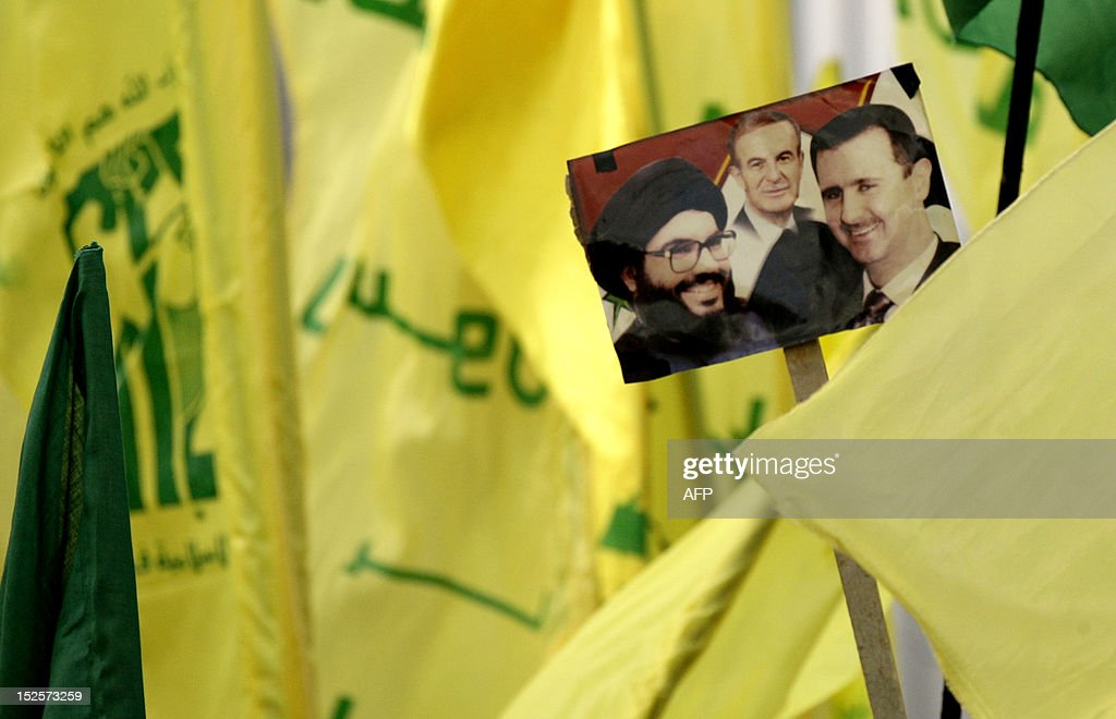 Lebanese Shiite Muslim movements' Hezbollah and Amal supporters (not seen) hold a picture of Hezbollah leader Hassan Nasrallah (L), Syrian President Bashar al-Assad (R) and his late father president Hafez al-Assad (C) in the southern town of Bint Jbeil on September 22, 2012, to protest against a US-made film mocking Islam and cartoons of the Prophet Mohammed which were published in a French magazine. Lebanese Muslims, Sunnis and Shiites, took to the streets across the country this past week to vent their anger.