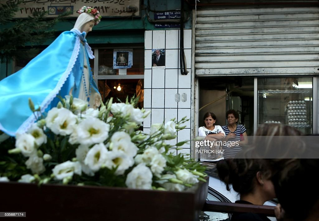 Lebanese shop owners look at Christian women carrying a statue of Virgin Mary during a procession marking the month of Virgin Mary in a Beirut Christian dominated neighbourhood on May 30, 2016. / AFP / PATRICK BAZ