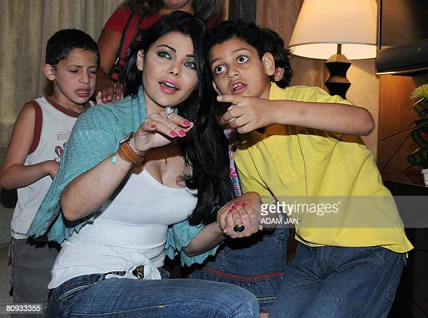 Lebanese singer Haifa Wehbe meets children with special needs during her visit to a care centre for children in Manama on April 29 2008 Bahrain's...