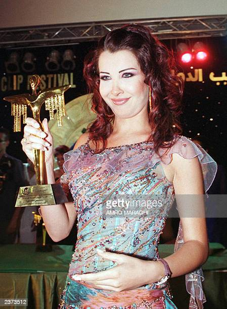Lebanese singer Nancy Agram displays her award after winning the first prize for best video clip and best Arab singer during the Fourth Video Clip...