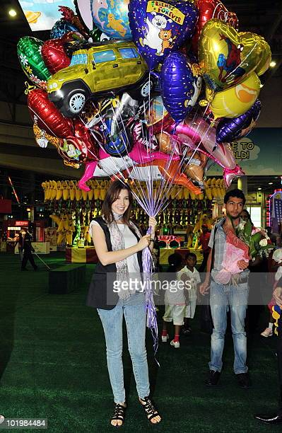 Lebanese singer Nancy Ajram holds balloons during her visit to Mudhish city a children's fun fair in Dubai June 10 2010 AFP PHOTO/STR