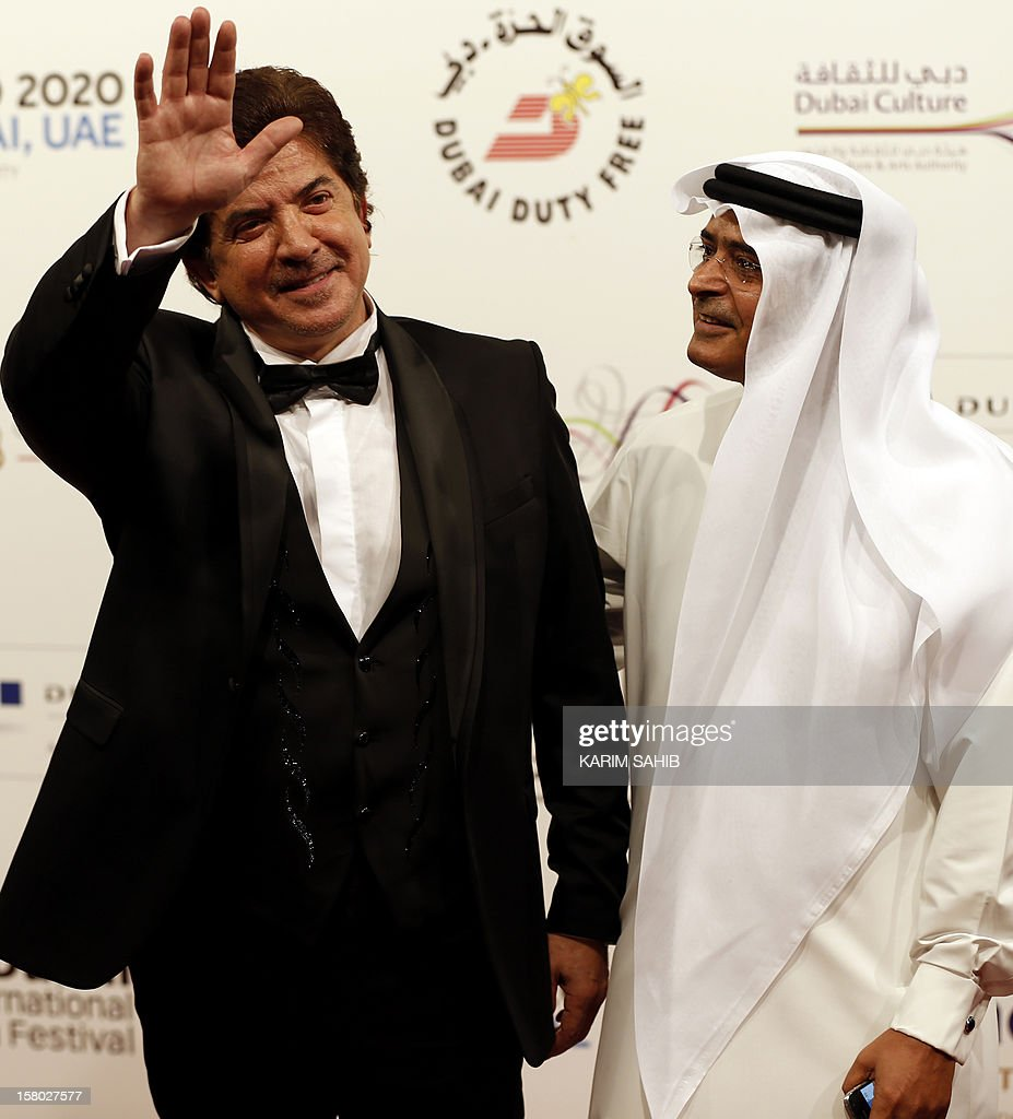 Lebanese singer Walid Toufic (L) waves to photographers as the Chairman of the Dubai International Film Festival Abdulhamid Juma watches on during the opening ceremony of the Dubai International Film Festival in Gulf emirate of Dubai on December 9, 2012. AFP PHOTO/KARIM SAHIB