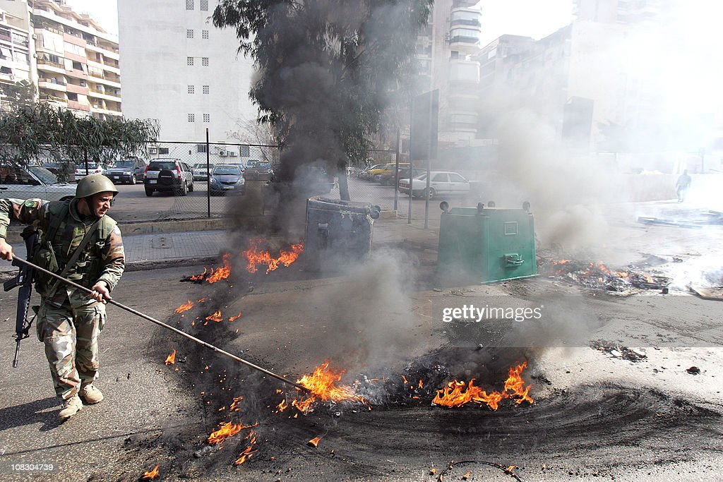 A Lebanese soldier disperses burning tires set alight by supporters of the Future Movement in a neighborhood in the capital Beirut during a demonstration in support of the caretaker prime minister Saad Hariri on January 25, 2011, as hundreds of people converged on the northern city of Tripoli to take part in a 'day of rage' over the likely appointment as prime minister of Hezbollah-backed tycoon Najib Mikati.