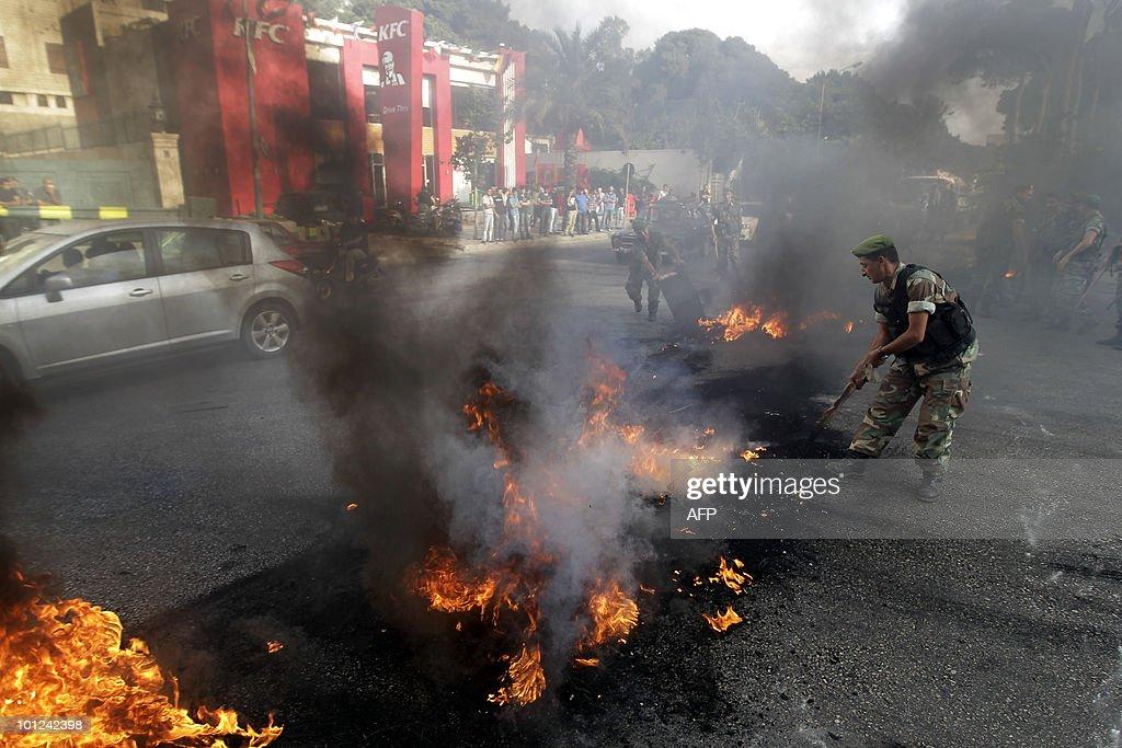 A Lebanese soldier from the Quick Intervention Squad tries to extinguish burning tires which were lit by residents of Beirut's southern suburb on May 28, 2010 during a demonstration against electricity cuts in their neighbourhoods.