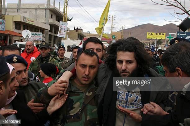 A Lebanese soldier helps a fellow member of the security forces who was kidnapped by jihadist groups from the eastern border town of Arsal last year...