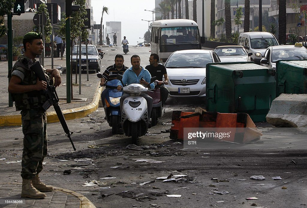 A Lebanese soldier stands guard as men ride motorcycles past trash containers blocking a road in the Corniche al-Mazraa neighbourhood of Beirut on October 20, 2012 following a protest against a bomb blast the day before. Protesters cut off roads in several areas of Lebanon following the assassination of a high profile security official, AFP journalists said.