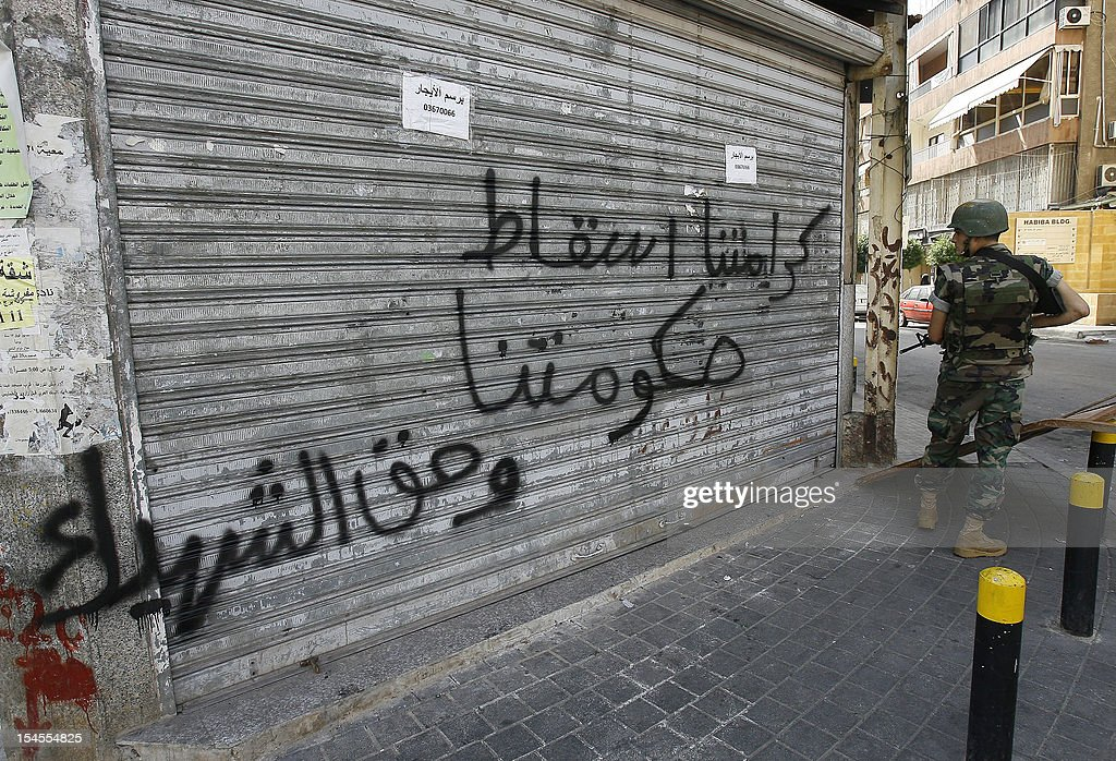 "A Lebanese soldier stops to look at graffiti that reads in Arabic, 'Our honor is in the fall of our government, and the right of the martyrs"" during a patrol of the Corniche al-Mazraa neighbourhood in the capital Beirut on October 22, 2012. The army said it was determined to restore order in Lebanon, roiled by growing political tensions linked to Syria after a top policeman was murdered and former premier Rafiq Hariri called for the government to step down. AFP PHOTO / STR"