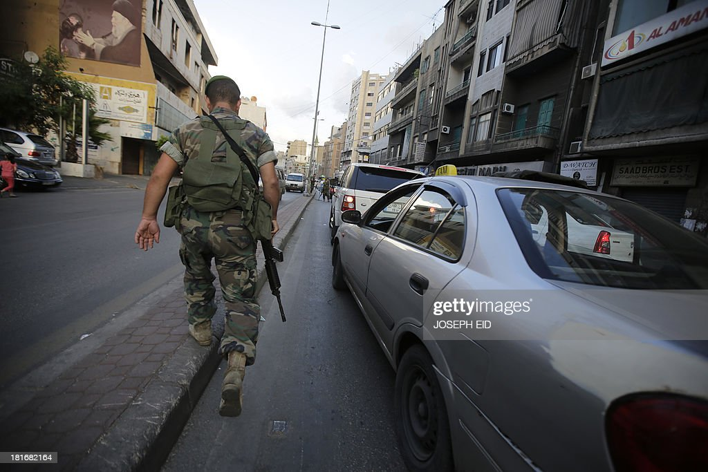 A Lebanese soldier walks towards a checkpoint in the southern suburb of the capital Beirut on September 23, 2013. Lebanese troops are to take over security at checkpoints set up by the Hezbollah movement in their southern Beirut stronghold after two bombings, the interior minister told AFP. AFP PHOTO/JOSEPH EID