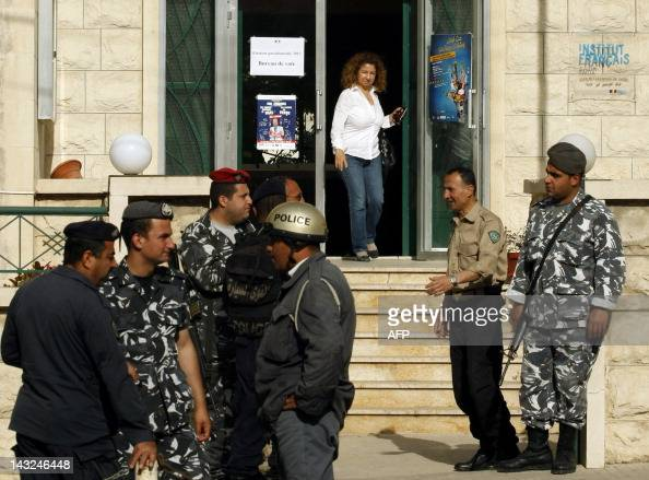 Lebanese soldiers and policemen stand guard as a French national woman residing in Lebanon leaves a polling station at the French cultural centre...