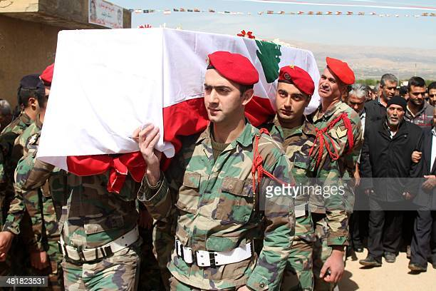 Lebanese soldiers carry the coffin of their comrade Mahmoud Ibrahim Hajj Hassan who died in a suicide bombing during his funeral on April 1 2014 in...