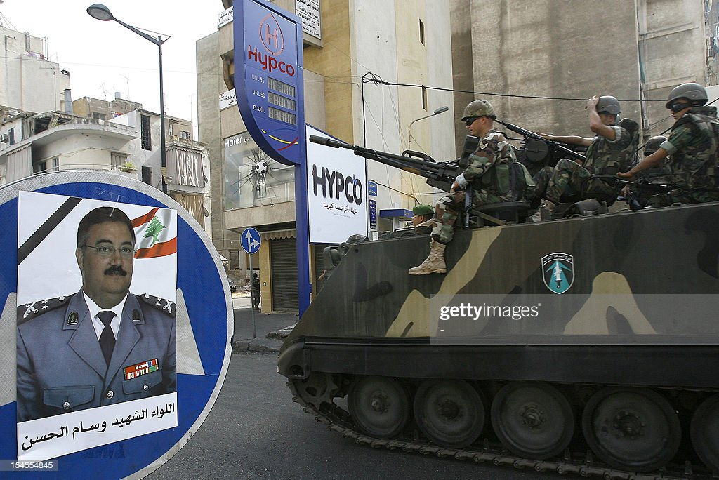 Lebanese soldiers drive by a portrait of assassinated official Wissam al-Hassan during a patrol in the Corniche al-Mazraa neighbourhood of the capital Beirut, on October 22, 2012. The army said it was determined to restore order in Lebanon, roiled by growing political tensions linked to Syria after a top policeman was murdered, and former premier Rafiq Hariri called for the government to step down.