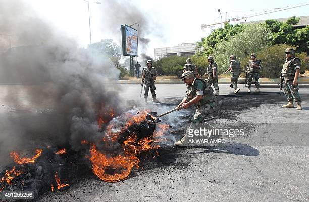 Lebanese soldiers remove burning tires from the old airport road in Beiruts southern suburbs on October 4 2015 as relatives of Lebanese soldiers and...