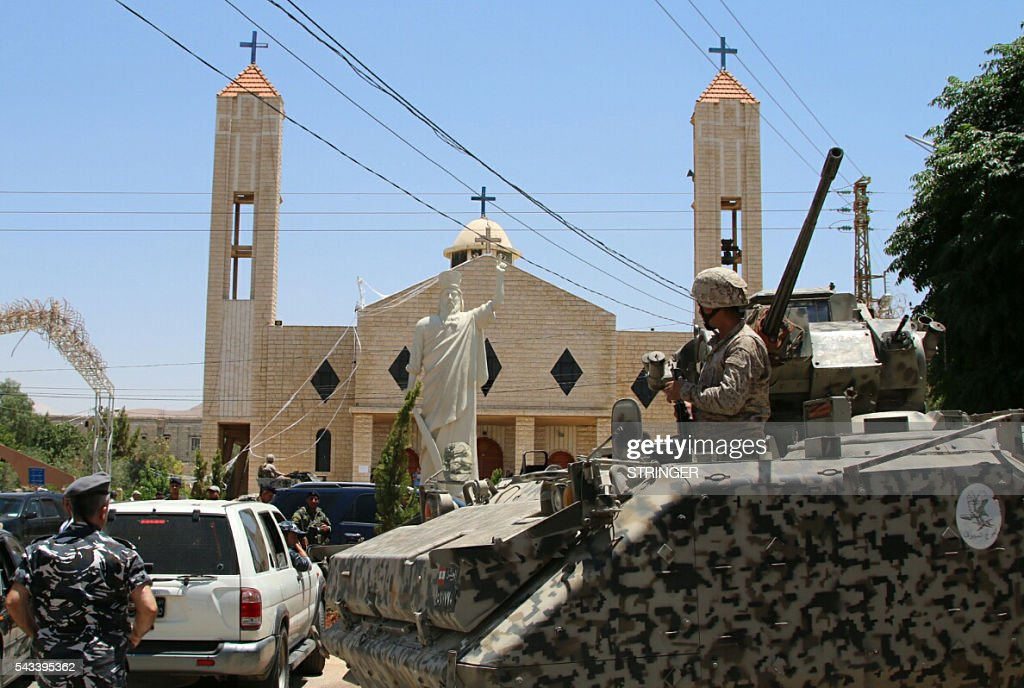 Lebanese soldiers stand guard in front of a church where a suicide bomber blew himself up the previous day in the Christian village of al-Qaa, near the Lebanon's border with war-ravaged Syria, on June 28, 2016. At least five people were killed and 15 wounded in the pre-dawn attacks in the eastern village of Al-Qaa, in a hilly border area shaken by violence since Syria's conflict erupted in 2011. A security source said two of the attacks were near the municipality building in the centre of the village. / AFP / STRINGER