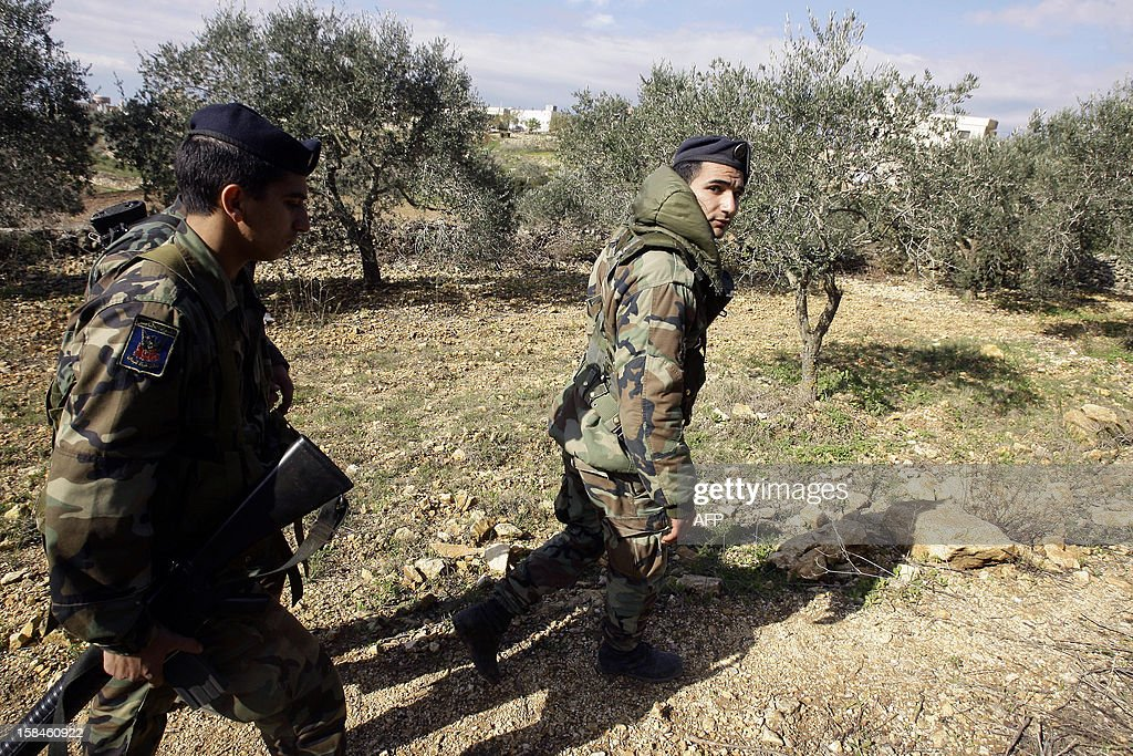 Lebanese soldiers walk in a field to inspect the site of a blast in the southern Lebanese village of Tair Harfa on December 17, 2012. An Israeli missile fired during the 2006 summer war between Israel and Lebanon's Hezbollah exploded in the village, causing material damage, according to a Lebanese security source. AFP PHOTO/MAHMOUD ZAYYAT