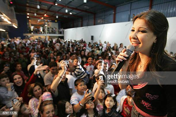 Lebanese star Nancy Ajram sings 10 April 2005 for children in downtown Beirut during a series of events commemorating the 30th anniversary of the...
