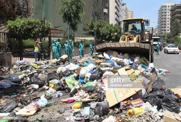 Lebanese street cleaners start to collect rubbish from the streets of Beirut a week after protesters shut down the country's largest landfill leaving...