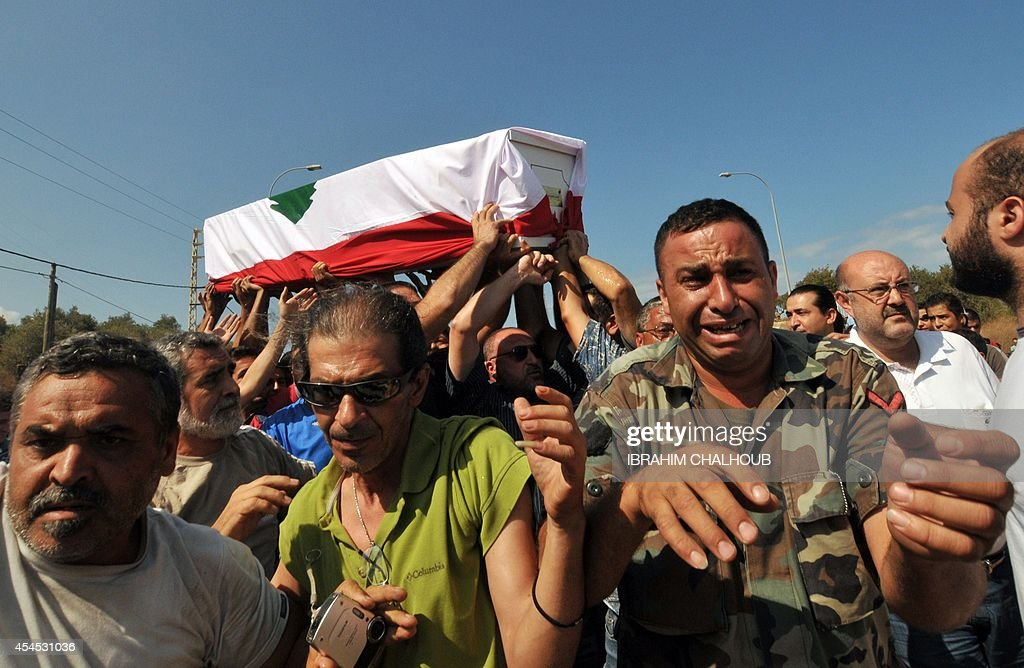 Lebanese Sunni mourners carry the coffin of Lebanese soldier Ali Sayyed draped in his national flag in the village of Qalamun south of the northern Lebanese city of Tripoli during his funeral procession on September 3, 2014. DNA testing confirmed that the body of man who jihadist said they had beheaded was that of Sayyed who was captured along with more than 20 other members of the Lebanese security forces in the eastern town of Arsal last month. AFP PHOTO / IBRAHIM CHALHOUB
