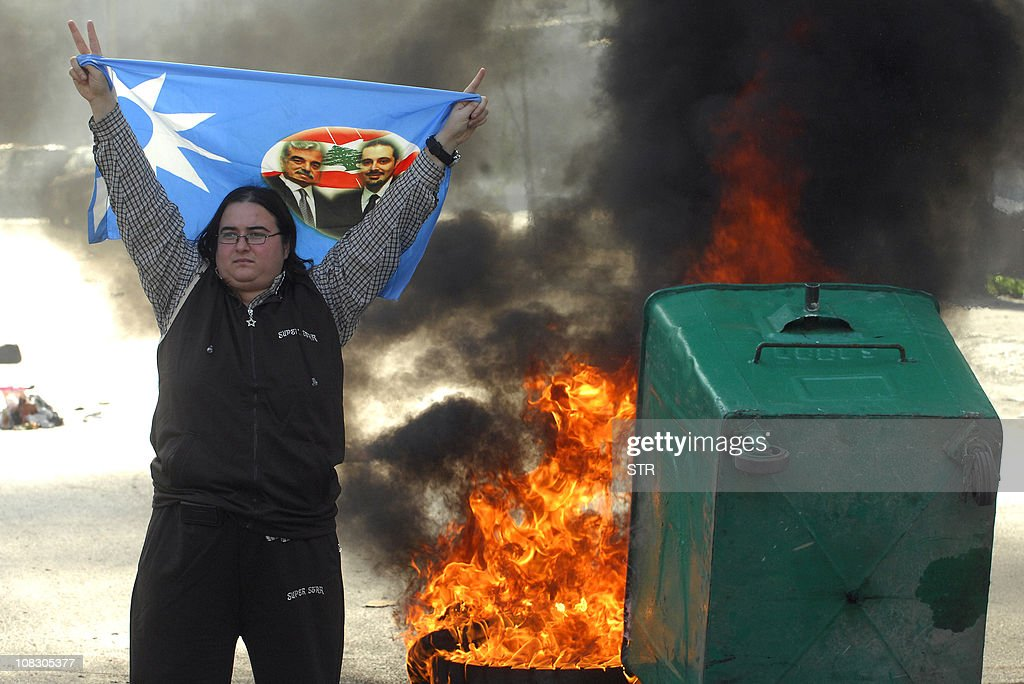 A Lebanese supporter of the Future Movement holds a party flag showing portraits of caretaker prime minister Saad Hariri (R) and his slain father former prime minister Rafiq Hariri near a burning garbage container during a protest in Beirut on January 25, 2011, as hundreds of people converged to the northern city of Tripoli to take part in a 'day of rage' over the appointment as prime minister of Hezbollah-backed tycoon Najib Mikati.