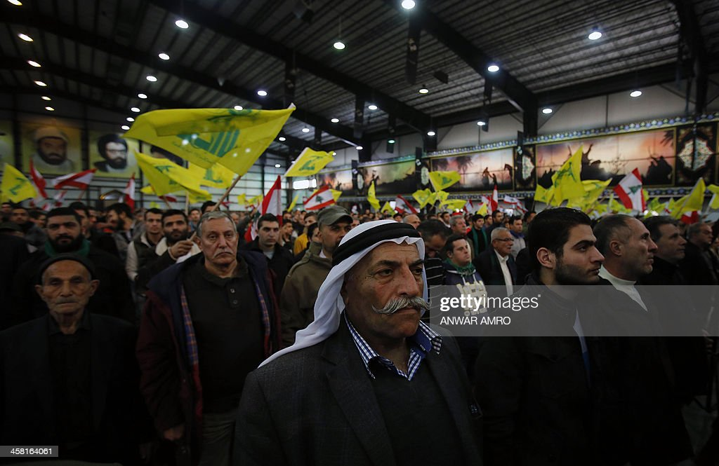 Lebanese supporters of the Shiite Hezbollah movement wave the movement's flag as they watch its chief Hassan Nasrallah, giving a televised speech on the December 4 murder of a top member of the movement, Hassan Hawlo al-Lakiss, in Beirut on December 20, 2013. Nasrallah warned that his Lebanese Shiite movement will 'punish' Israel for the killing of a top leader earlier this month.
