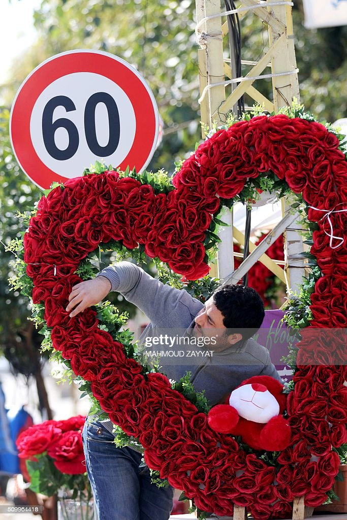 A Lebanese vendor decorates a heart with red roses on the eve of the Valentine's day on February 13, 2016 in the southern Lebanese city of Sidon. ZAYYAT