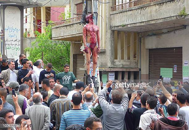 Lebanese villagers take pictures with their mobile phones of a lynched Egyptian murder suspect after he was hung by his killers with a butcher's hook...