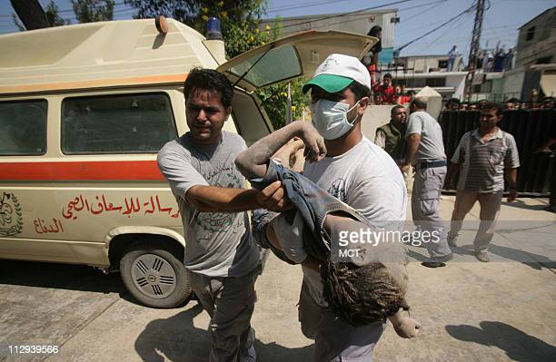 Lebanese volunteers carry the body of a child to a hospital in the port city of Tyre Lebanon Sunday July 30 after an Israeli air strike killed at...