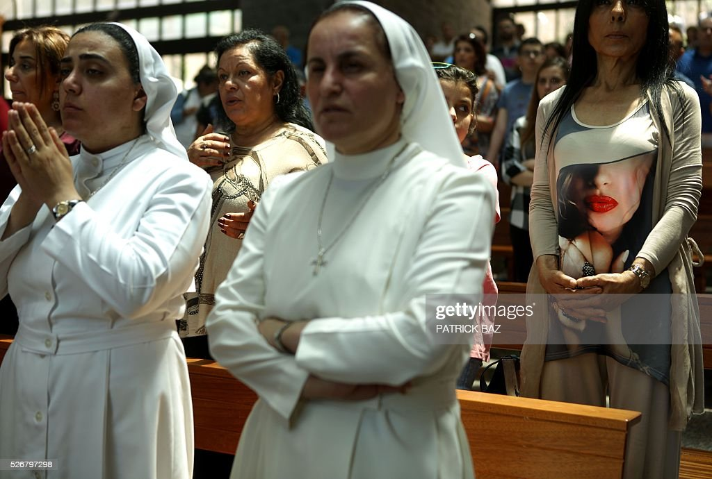 A Lebanese woman and Maronite Christian nuns attend a prayer at the basilica of Our Lady of Lebanon in the town of Harissa north east of the Lebanese capital Beirut, marking the start of the Holy Month of Virgin Mary, on May 1, 2016. / AFP / PATRICK BAZ