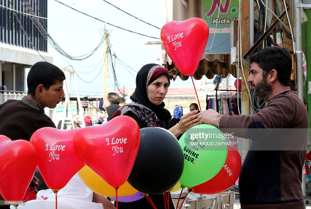 A lebanese woman buys a balloon on the eve of the Valentine's day on February 13, 2016 in the southern Lebanese city of Sidon. ZAYYAT