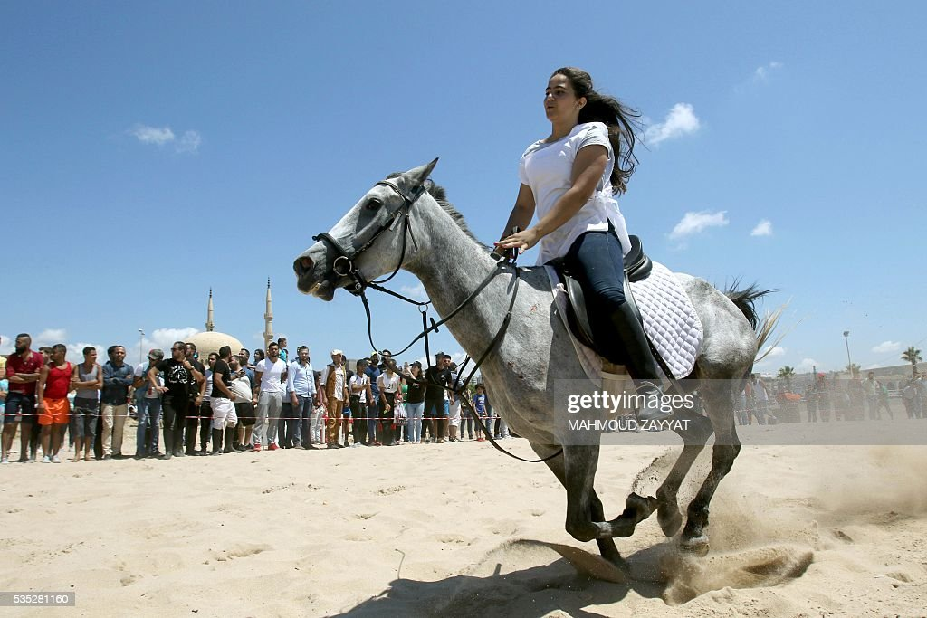 A Lebanese woman competes during a horse race festival on the coast shore of the city of Sidon, south Lebanon, on May 29, 2016. ZAYYAT