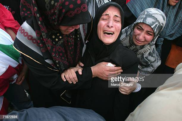 Lebanese woman cries at the grave yard as she burries one of her relatives one of the victims of the Qana air raid during the funeral on August 18...