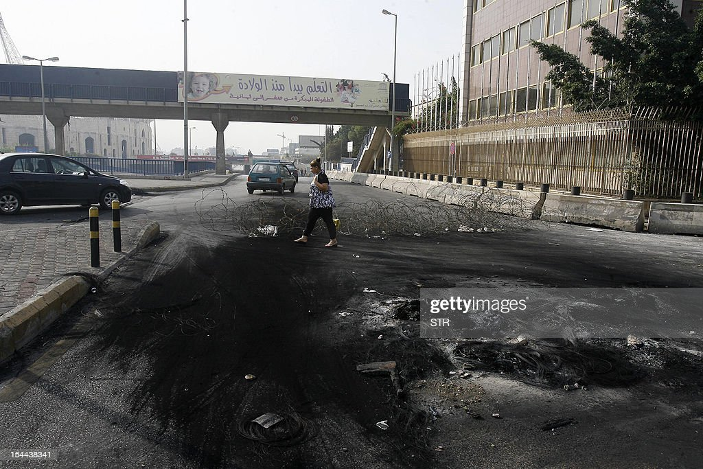 A Lebanese woman crosses a blocked road where tyres were burnt by protesters demonstrating against a bomb blast in Beirut on October 20, 2012. Protesters cut off roads in several areas of Lebanon following the assassination of a high profile security official, AFP journalists said. AFP PHOTO/STR