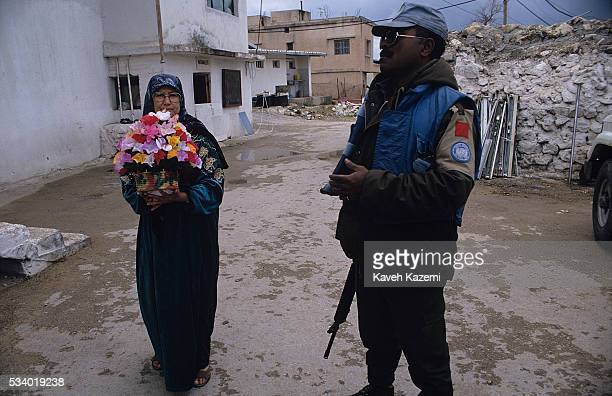 A Lebanese woman holding flowers in her hands stands next to a UN peacekeepers on the site of the UN camp in Qana where Israeli missile was fired on...