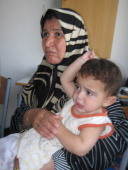 A Lebanese woman holds her 11monthold grandson Hassan hours after they arrived Saturday at a school in Sidon Lebanon on Saturday July 22 2006 Many...