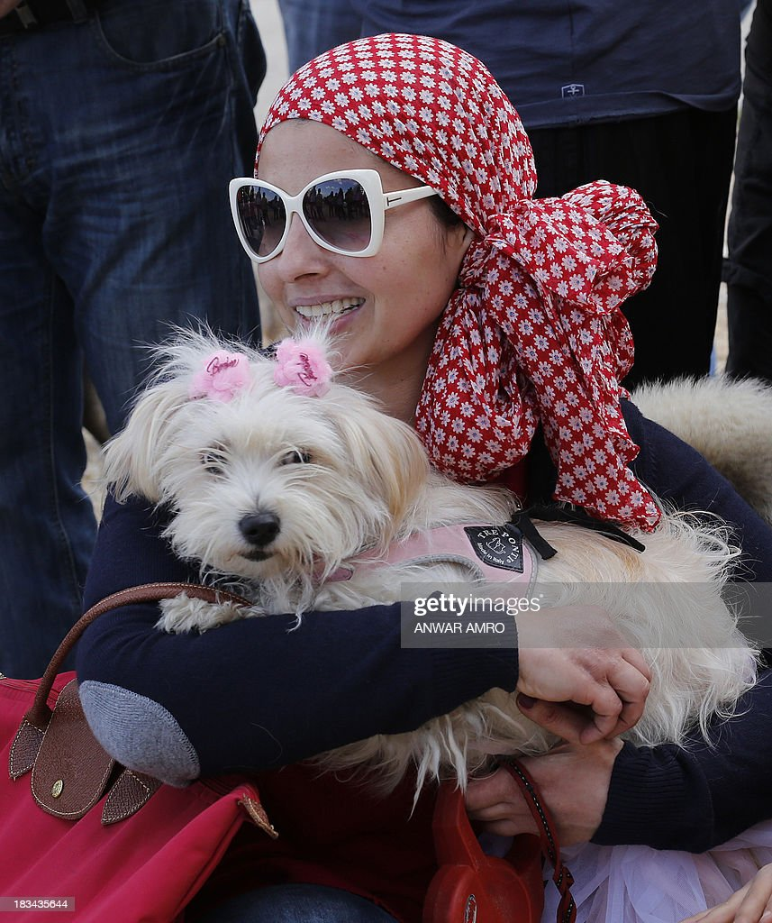 A Lebanese woman holds her dog in Martyr's Square in downtown Beirut at the start of march along the Corniche organised by Beirut for the Ethical Treatment of Animals (BETA) on October 6, 2013 in support of the improvement of animal welfare in the region and to stop the abuse against them.