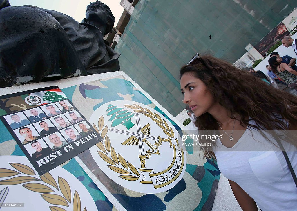 A Lebanese woman looks up at a poster with the images of some of the Lebanese Army soldiers killed in clashes with supporters of radical Sunni cleric Ahmad al-Assir, during a gathering to show solidarity with the army, on June 25, 2013, in Martyr's Square, in downtown Beirut.Several hundred people gathered to show their support for the Lebanese army a day after 17 soldiers were killed in the clashes in the southern port city of Sidon.