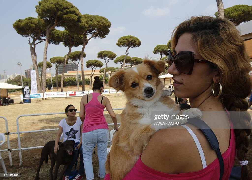 A Lebanese woman poses with her dog during the Beirut for the Ethical Treatment of Animals (BETA) dog show in Beirut, which holds contests to name 'best dog', 'cutest puppy', and 'best dog costume' in addition to 12 other categories on June 29, 2013. The show is one of BETA's major fundraisers to try to improve the welfare of animals in the region and to stop the abuse against them.