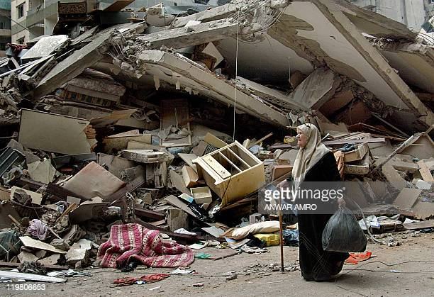 A Lebanese woman reacts as she walks in front wreckage of a destroyed building in Beirut's southern suburb 26 August 2006 The bitter smell of burned...