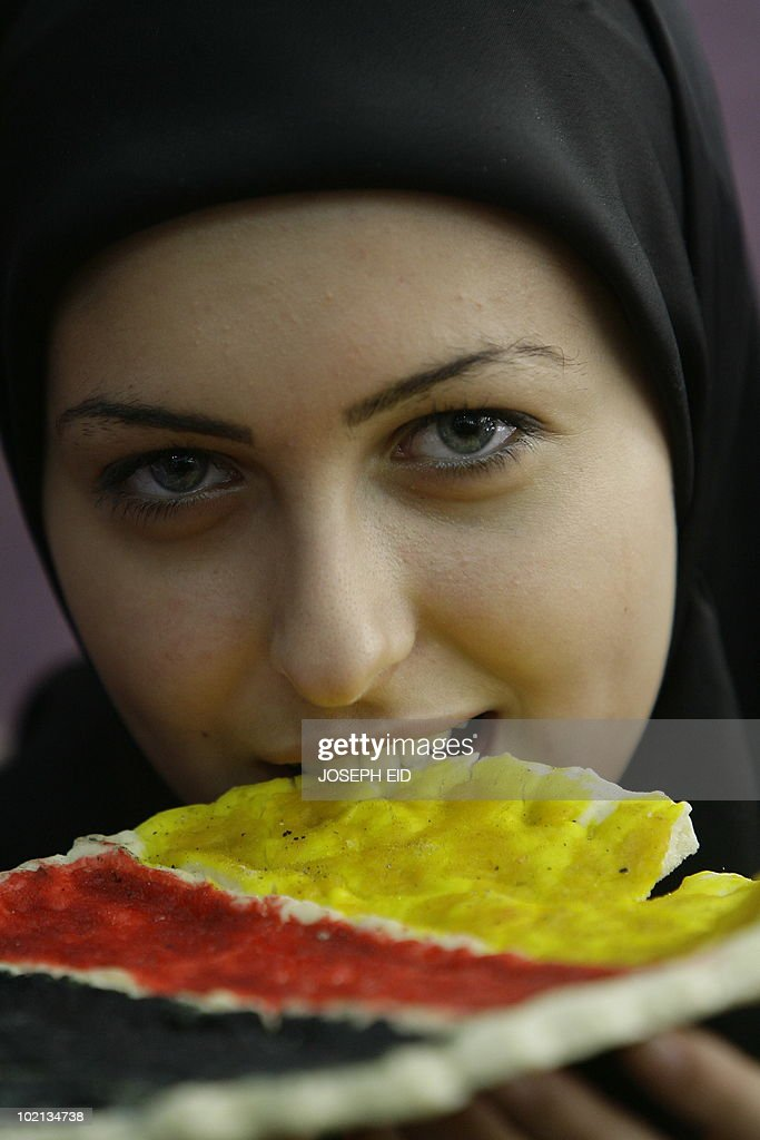 A Lebanese woman samples a 'special-edition World Cup 2010' traditional Lebanese oven-baked flat bread, covered with cheese and decorated with the German flags, at a bakery in a southern suburb of Beirut on June 16, 2010.