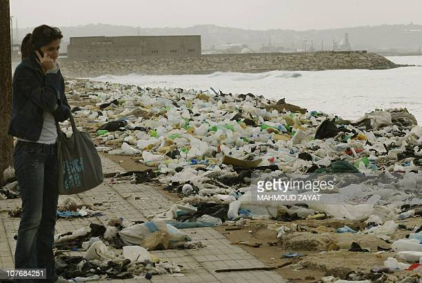 A Lebanese woman speaks on her mobile phone as she stands close to a garbage dump spilling into the Mediterranean sea in the southern Lebanese city...