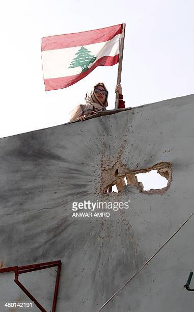A Lebanese woman stands on the roof of her family home as she inspects the damage of rocketpropelled grenade near the capital's Tariq Jedideh...