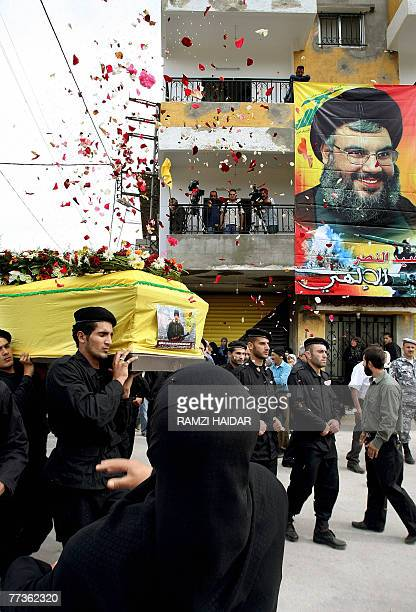 A Lebanese woman throws rose petals onto the coffin of Hezbollah militant Mohammed Aussayli during his funeral procession in the southern Lebanese...