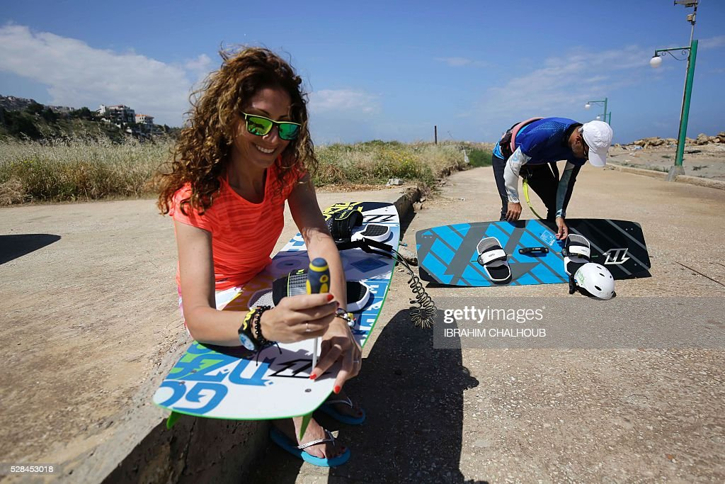 A Lebanese woman uses a screwdriver on her surfboard in the northern port city of Tripoli, on May 5, 2016. / AFP / IBRAHIM