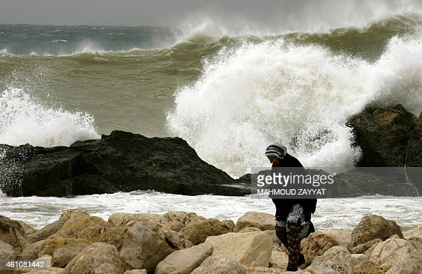 A Lebanese woman walks on rocks near large waves hitting a seawall during a winter storm in the southern Lebanese city of Sidon on January 6 2015 AFP...